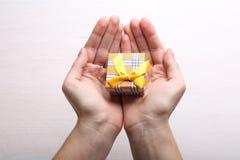 Boîte-cadeau dans des mains Images stock