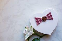 Boîte-cadeau dans la forme du coeur avec la fleur simple d'alstroemeria sur le mA Photographie stock libre de droits