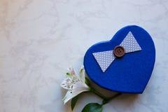 Boîte-cadeau dans la forme du coeur avec la fleur simple d'alstroemeria sur le mA Photographie stock