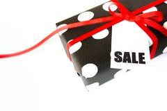 Boîte-cadeau dans les points de polka noirs et blancs Fond blanc, ri rouge Photographie stock