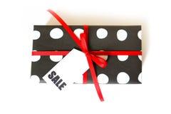 Boîte-cadeau dans les points de polka noirs et blancs Fond blanc, ri rouge Photo stock