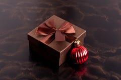 Boîte-cadeau de Brown et boule de Noël sur le fond noir, plan rapproché Photographie stock