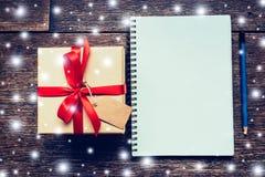 Boîte-cadeau de Brown et carnet, crayon avec le blanc de neige sur le verrat en bois Photos stock