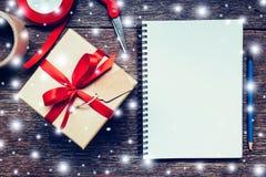 Boîte-cadeau de Brown et carnet, crayon avec le blanc de neige sur le verrat en bois Photographie stock libre de droits