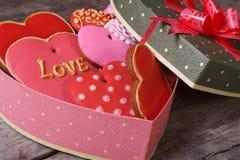 Boîte-cadeau de fête dans la forme de coeur avec des bonbons sur la table Image stock