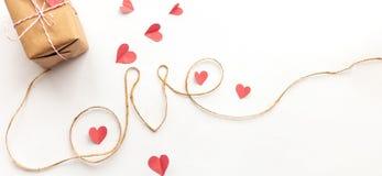 Boîte-cadeau de jour de valentines de cru sur le fond blanc avec l'arc de papier rose, corde de jute, lettres d'amour photographie stock
