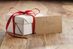 Boîte-cadeau de livre blanc avec la carte de papier rouge mince de ruban et du 8 mars sur la vieille table en bois Image libre de droits