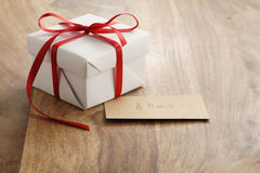 Boîte-cadeau de livre blanc avec la carte de papier rouge mince de ruban et du 8 mars sur la vieille table en bois Photo libre de droits