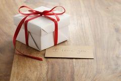 Boîte-cadeau de livre blanc avec le ruban rouge mince et je t'aime carte de papier sur la vieille table en bois Image libre de droits