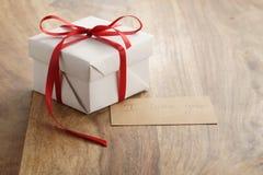 Boîte-cadeau de livre blanc avec le ruban rouge mince et je t'aime carte de papier sur la vieille table en bois Image stock