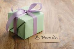 Boîte-cadeau de Livre vert avec l'arc pourpre de ruban et carte de voeux du 8 mars sur la vieille table en bois Image libre de droits