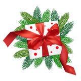 Boîte-cadeau de maille de réalisme de vecteur de Noël avec un arc rouge sur des branches d'arbre de Noël sur le fond blanc d'isol Photo libre de droits