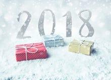 Boîte-cadeau de Noël, actuel sur la neige avec le fond 2018 Photographie stock