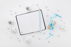 Boîte-cadeau de Noël avec le ruban bleu, le carnet vide et le tintement du carillon sur la table blanche ci-dessus Carte de voeux Images stock