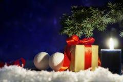 Boîte-cadeau de Noël avec le ruban rouge et boules sur la neige sur le fond de nuit Image stock