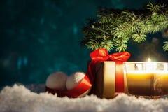 Boîte-cadeau de Noël avec le ruban rouge et boules sur la neige sur le fond de nuit Photos stock
