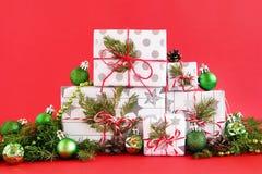 Boîte-cadeau de Noël sur un fond rouge, décoré des branches de sapin, des cônes de pin et des décorations vertes brillantes de No image libre de droits