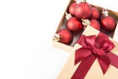 Boîte-cadeau de papier avec un arc rouge et des boules de Noël, sur le fond blanc Photos stock