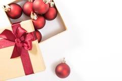 Boîte-cadeau de papier avec un arc rouge et des boules de Noël, sur le fond blanc Photographie stock