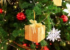 Boîte-cadeau de place de scintillement d'or mini avec d'autres ornements colorés de Noël sur un arbre de Noël de scintillement Photo libre de droits