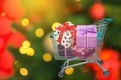 Boîte-cadeau de ruban de cadeaux et de présents de Noël dans le chariot de chariot à achats avec les lumières brouillées Image stock