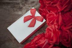Boîte-cadeau de Valentine sur la table en bois avec le bouquet de roses rouges pour l'amour Photographie stock