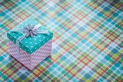 Boîte-cadeau emballé sur le concept vérifié de célébrations de textile Photographie stock