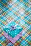 Boîte-cadeau emballé sur le concept vérifié de vacances de textile Photographie stock