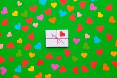 Boîte-cadeau emballé sur un fond vert avec beaucoup de coeurs multicolores autour Image libre de droits