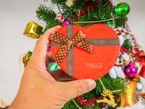 Boîte-cadeau en forme de coeur à disposition sur le fond d'arbre de Noël Photos libres de droits