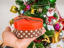 Boîte-cadeau en forme de coeur à disposition sur le fond d'arbre de Noël Photo libre de droits
