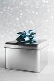 Boîte-cadeau en métal sur le fond blanc de scintillement Boîte-cadeau en métal sur le fond blanc de scintillement Carte de Joyeux Photo stock