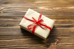 Boîte-cadeau enveloppé dans le papier d'emballage et le ruban rouge sur le backgro en bois photos stock