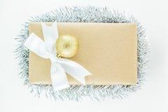 Boîte-cadeau enveloppé de vintage avec l'arc blanc de ruban, ornement argenté de tresse sur un fond blanc Photographie stock libre de droits