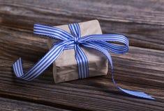 Boîte-cadeau enveloppé en papier naturel avec le ruban bleu Images stock