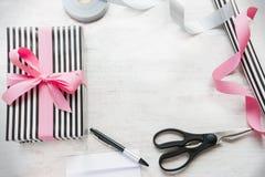 Boîte-cadeau enveloppé en papier rayé noir et blanc avec les matériaux roses de ruban et d'emballage sur un vieux fond en bois bl image stock