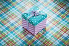 Boîte-cadeau enveloppé sur le conce vérifié de célébrations de fond de tissu Photo libre de droits