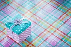 Boîte-cadeau enveloppé sur le concept vérifié de vacances de fond de tissu Photos libres de droits