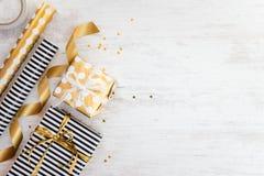 Boîte-cadeau enveloppés en matériaux pointillés rayés et d'or noirs et blancs de papier et d'emballage sur un vieux fond en bois  Photographie stock libre de droits