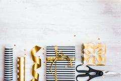 Boîte-cadeau enveloppés en matériaux pointillés rayés et d'or noirs et blancs de papier et d'emballage sur un vieux fond en bois  Images libres de droits