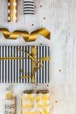 Boîte-cadeau enveloppés en matériaux pointillés rayés et d'or noirs et blancs de papier et d'emballage sur un vieux fond en bois  Photos libres de droits