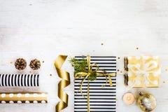 Boîte-cadeau enveloppés en papier pointillé avec, pin, cônes, bougie et matériaux d'emballage rayés et d'or noirs et blancs sur u Photo libre de droits