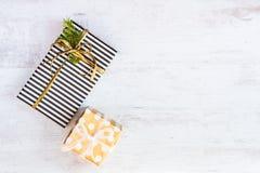 Boîte-cadeau enveloppés en papier pointillé rayé et d'or noir et blanc sur un fond en bois blanc Weihnachtspakete - cadeau de Noë photographie stock libre de droits