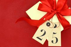 Boîte-cadeau et étiquettes avec le numéro 25 sur le fond rouge Images stock