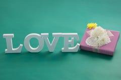 Boîte-cadeau et amour d'alphabet sur le fond vert Image stock
