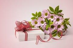 Boîte-cadeau et belles fleurs sur le fond rose Photographie stock libre de droits