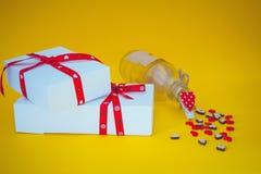 Boîte-cadeau et bouteille sur le fond jaune Image stock