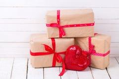 Boîte-cadeau et coeur décoratif rouge sur le fond en bois blanc Photographie stock