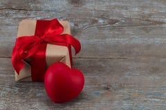 Boîte-cadeau et coeur rouge sur le fond en bois Bande rouge val Photo stock