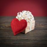 Boîte-cadeau et coeur sur le vieux fond en bois Photo stock